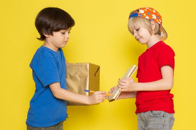 Una vista frontal de niños pequeños en camisetas rojas y azules, gorra de colores y jeans grises con caja en el fondo amarillo