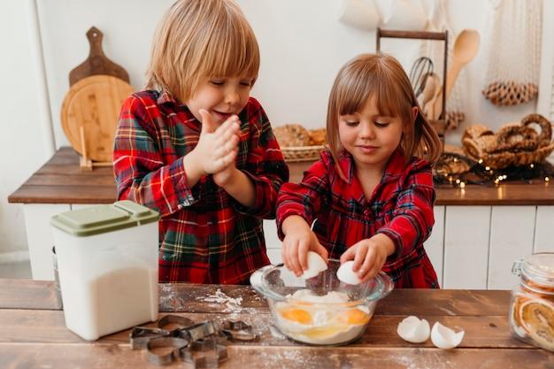 Vista frontal de los niños pequeños haciendo galletas de navidad