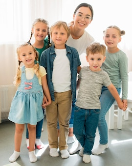 Vista frontal de los niños y el profesor posando juntos