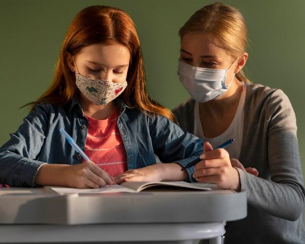 Vista frontal de niños que aprenden en la escuela con el maestro durante la pandemia de coronavirus
