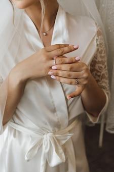 La vista frontal de una novia en la bata sedosa se pone el precioso anillo de compromiso