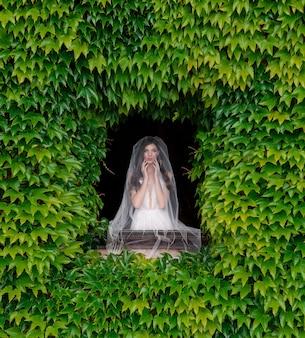 Vista frontal de la novia de pie ante la ventana con marco de vegetación fresca