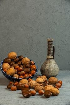 Vista frontal de nueces con cáscara de avellanas con castañas esparcidas de un jarrón con una jarra