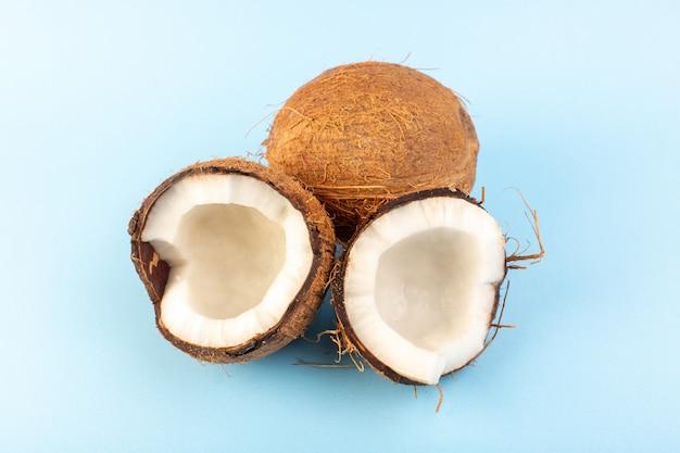 Una vista frontal de nueces de coco en rodajas y todo lechoso dulce fresco aislado en el fondo azul helado tuerca de frutas exóticas tropicales