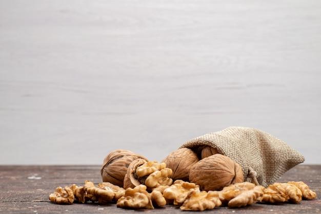 Vista frontal nueces enteras frescas en cáscaras y limpiadas en bocadillo gris de nueces y nueces