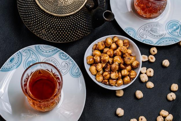 Vista frontal de nueces tostadas con miel y un vaso de té
