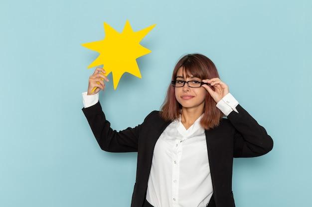 Vista frontal de la oficinista femenina con enorme cartel amarillo sobre superficie azul