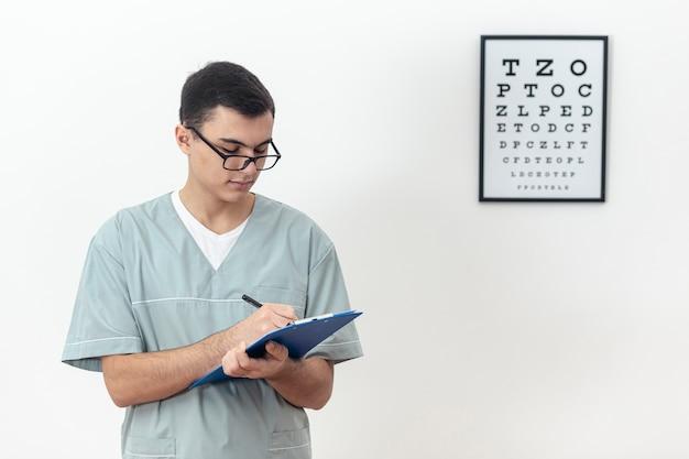 Vista frontal del oftalmólogo con bloc de notas y escritura