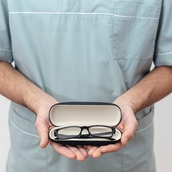 Vista frontal del oftalmólogo con par de anteojos en caso