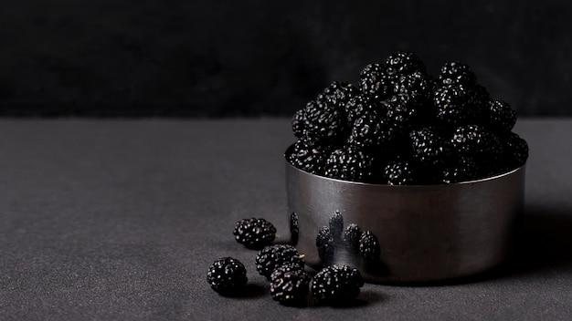 Vista frontal oscura deliciosas moras en un tazón