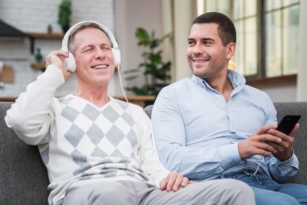 Vista frontal del padre disfrutando de la música del teléfono del hijo