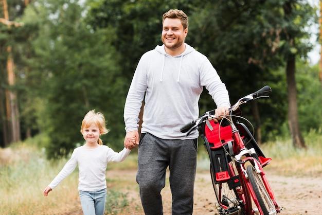 Vista frontal padre e hija caminando