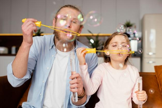 Vista frontal de padre e hija jugando con pompas de jabón