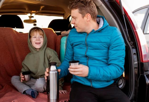 Vista frontal de padre e hijo en el coche bebiendo té durante un viaje por carretera