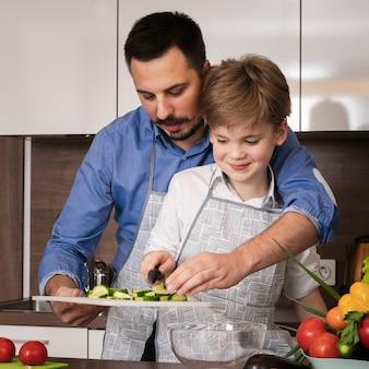 Vista frontal padre enseñando a hijo a cortar verduras