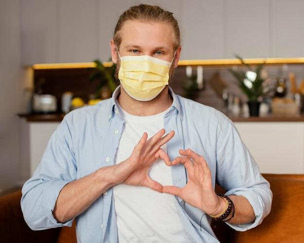 Vista frontal del padre con máscara médica haciendo signo de corazón con las manos