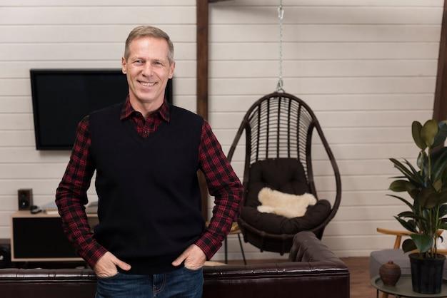 Vista frontal del padre sonriente posando en casa