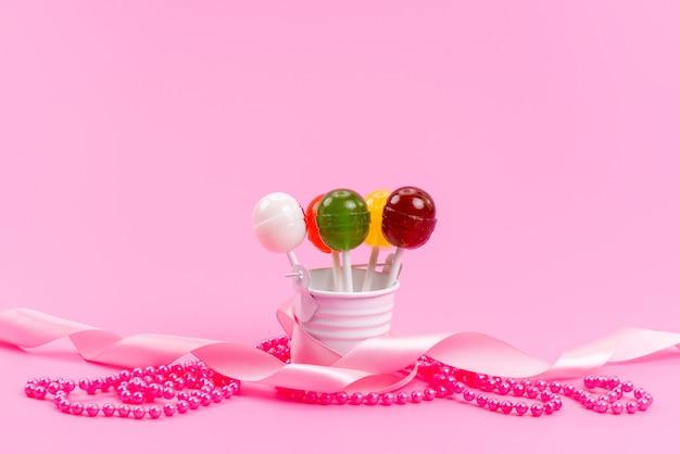 Una vista frontal de paletas de colores dentro de blanco, cubo en rosa, dulces de confitería dulce de azúcar