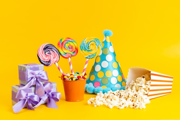 Una vista frontal de paletas y palomitas de maíz junto con una tapa azul, cajas de regalo moradas y dulces en amarillo