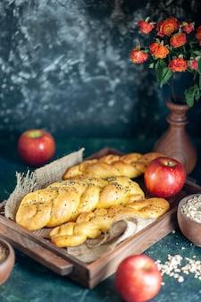 Vista frontal de palitos de pan de tejido de cable en un tablero de madera rectangular, manzanas, flores en un jarrón sobre la mesa