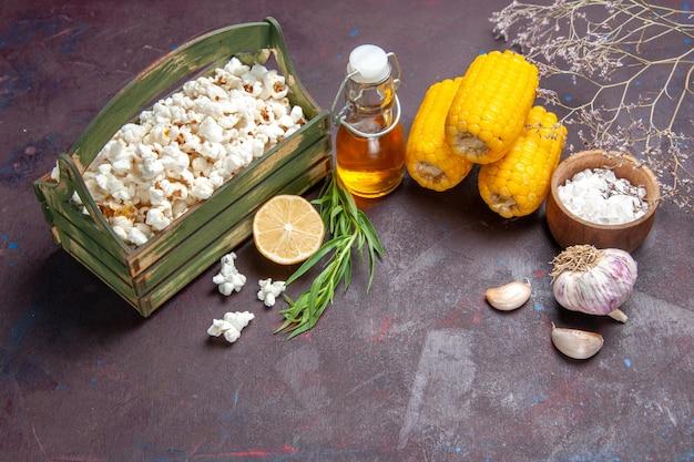 Vista frontal de palomitas de maíz frescas con granos amarillos en palomitas de maíz de aceite de película de snack de maíz de superficie oscura