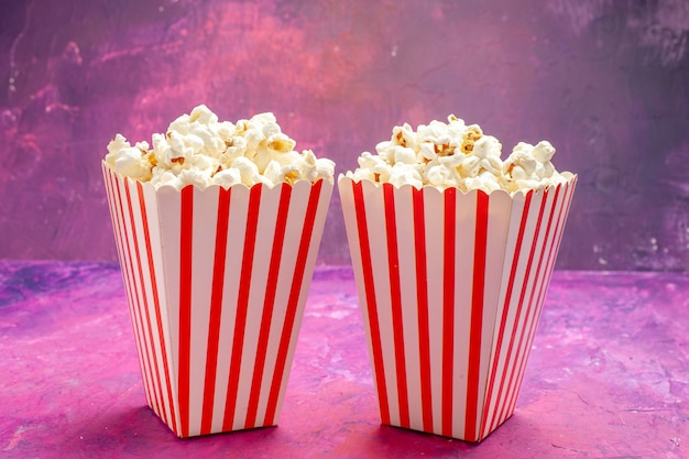 Vista frontal de palomitas de maíz frescas en la película de cine de color de mesa rosa