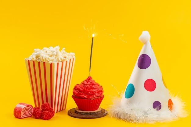 Una vista frontal de palomitas de maíz y pastel con gorro de cumpleaños y mermeladas en el escritorio amarillo