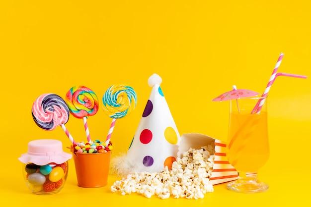 Una vista frontal de palomitas de maíz y piruletas junto con un divertido sombrero y cóctel en amarillo
