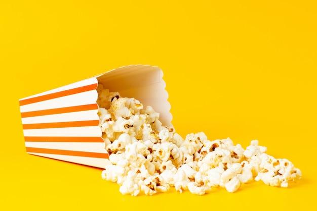 Una vista frontal de palomitas de maíz programadas dentro del paquete se extendió todo en amarillo
