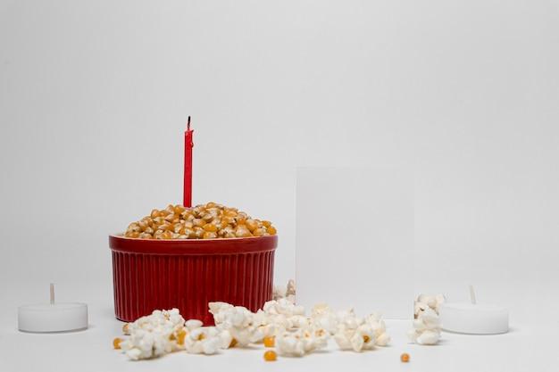 Vista frontal de palomitas de maíz con vela para celebración de lohri