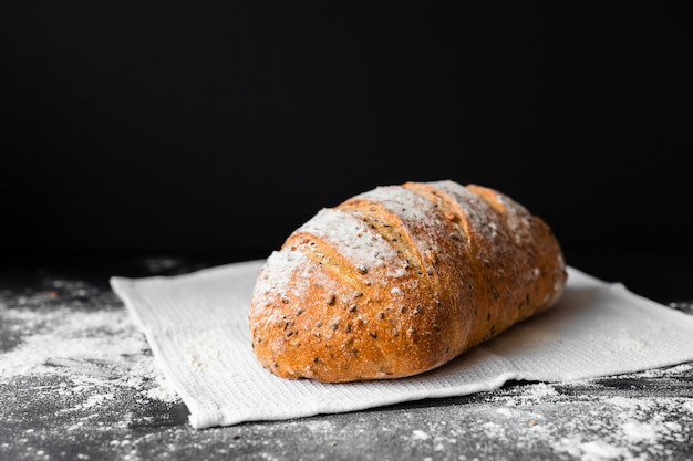 Vista frontal pan fresco sobre fondo negro y tela con harina