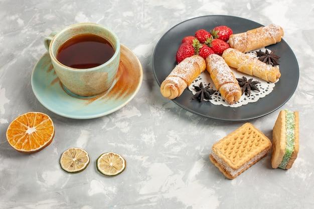 Vista frontal de panecillos de azúcar en polvo con fresas y una taza de té en el escritorio blanco
