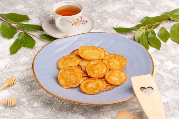 Vista frontal panqueques deliciosos dulces dentro de la placa azul en el escritorio gris comida para panqueques postre dulce