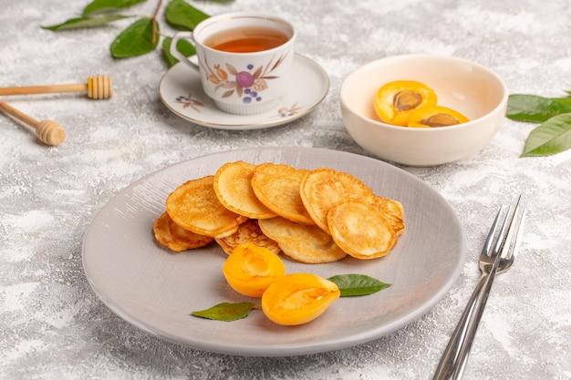 Vista frontal de panqueques dulces dentro de la placa con albaricoques y té en el escritorio gris comida de panqueques postre dulce fruta