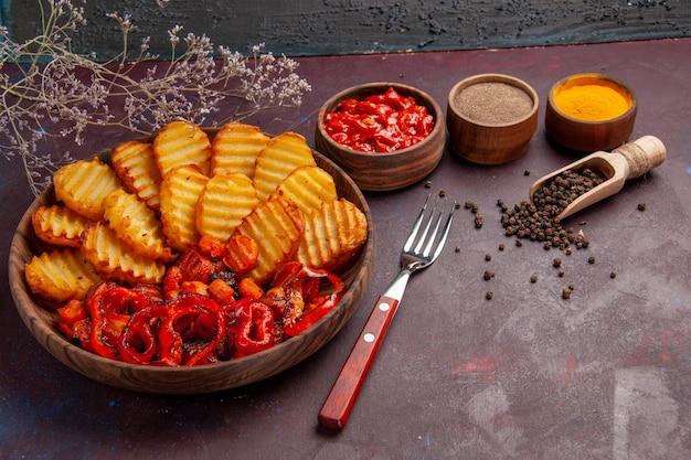 Vista frontal de papas al horno con verduras cocidas y condimentos en un espacio oscuro
