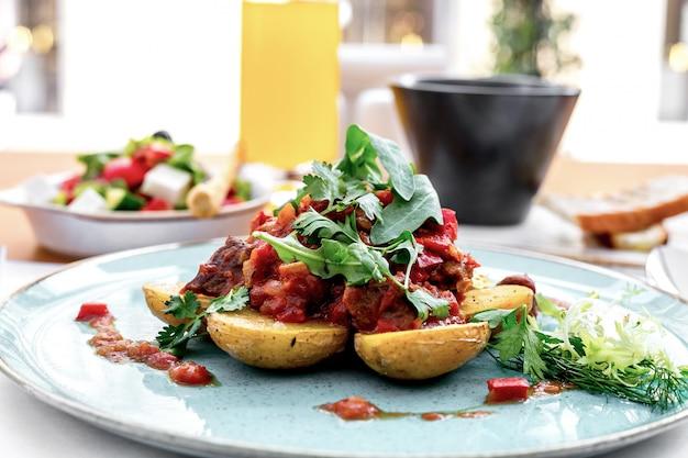 Vista frontal de papas con carne en salsa de tomate con rúcula y ensalada griega sobre la mesa