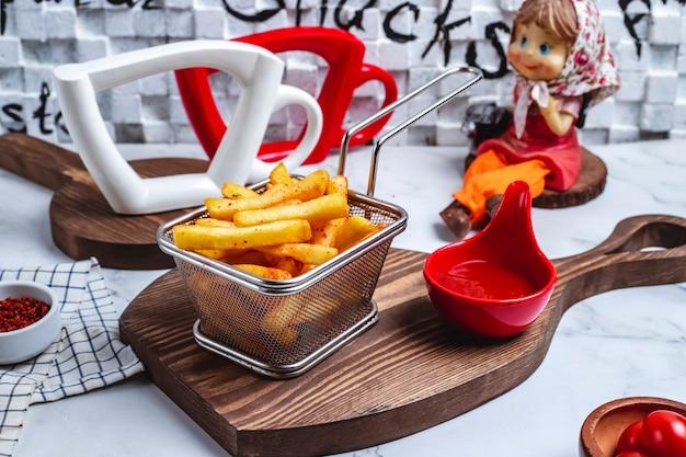 Vista frontal papas fritas en una canasta con salsa de tomate en el tablero