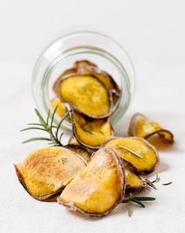 Vista frontal de papas fritas con romero en frasco