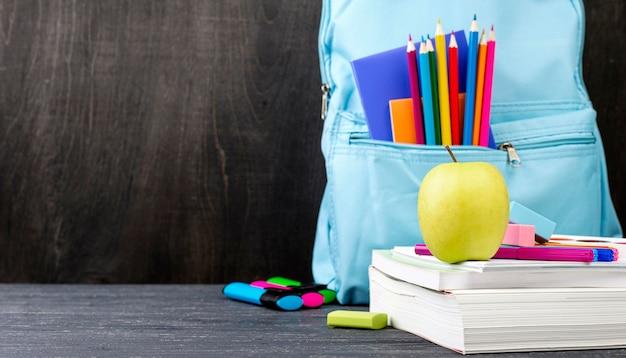 Vista frontal de papelería de regreso a la escuela con lápices de colores y manzana