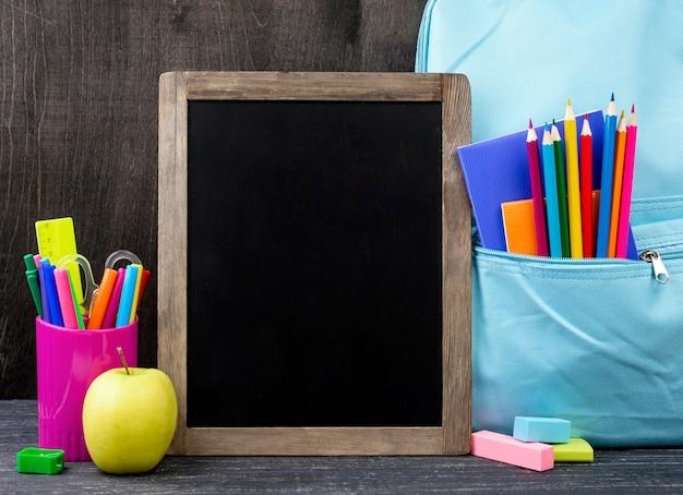 Vista frontal de papelería de regreso a la escuela con lápices de colores y pizarra