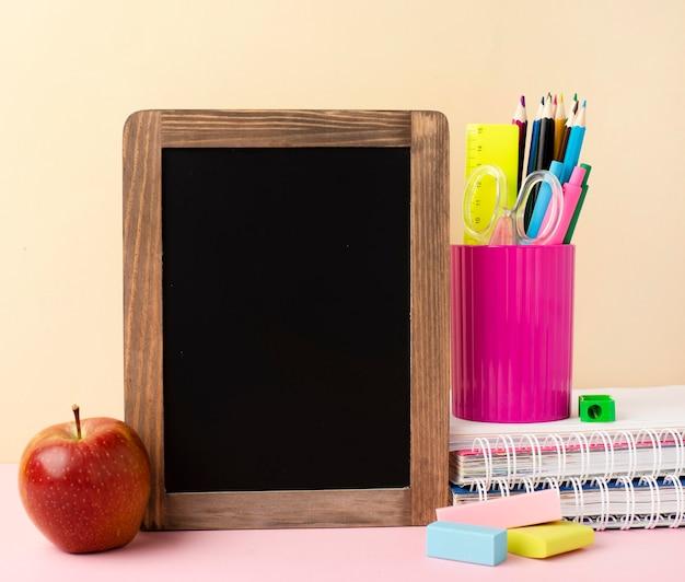 Vista frontal de papelería de regreso a la escuela con manzana y pizarra