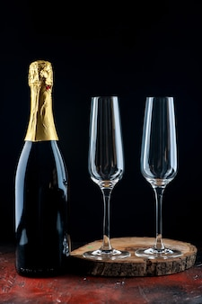 Vista frontal de un par de copas de champán en tablero de madera y botella de champán