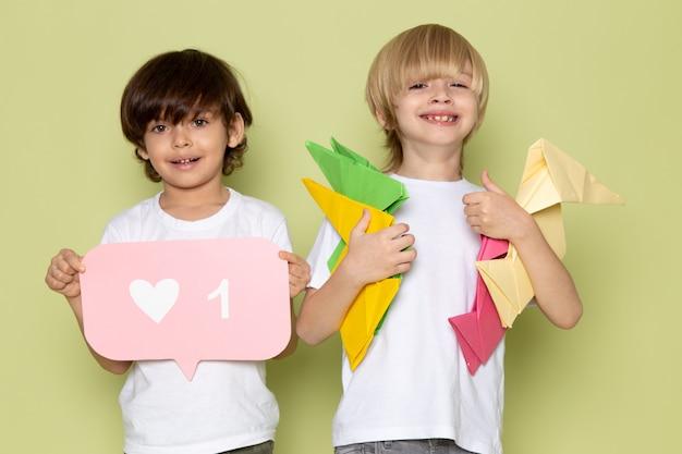 Una vista frontal par de muchachos sonriendo adorable dulce lindo feliz celebración de figuras de papel en el espacio de color piedra
