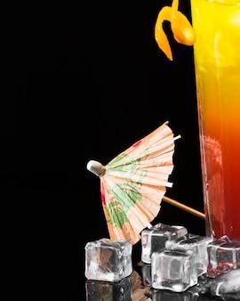 Vista frontal del paraguas con cubitos de hielo y cóctel