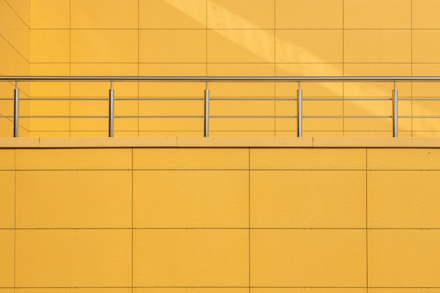 Vista frontal de la pared de azulejos de color amarillo cálido con barandilla de metal