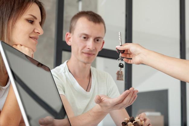 Vista frontal pareja aceptando las llaves de una casa nueva