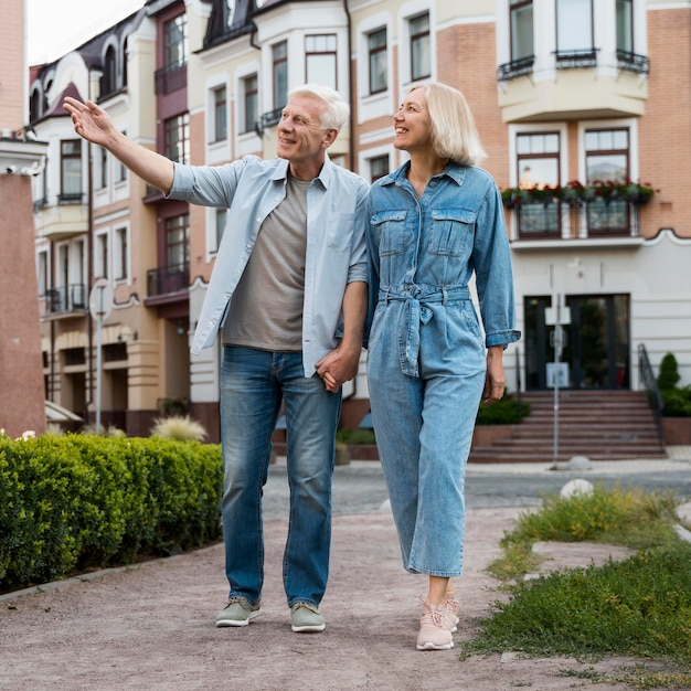 Vista frontal de la pareja de ancianos dando un paseo por la ciudad