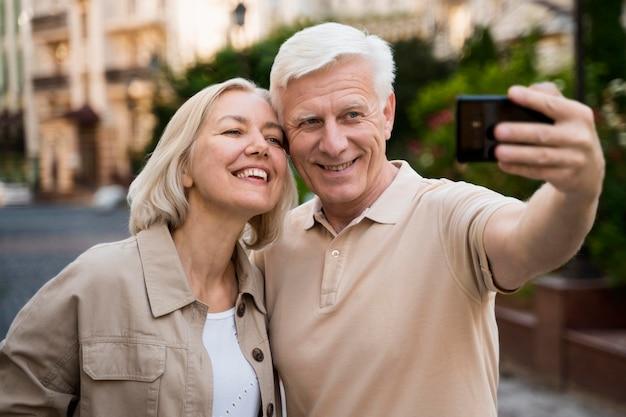 Vista frontal de la pareja de ancianos tomando un selfie mientras está en la ciudad