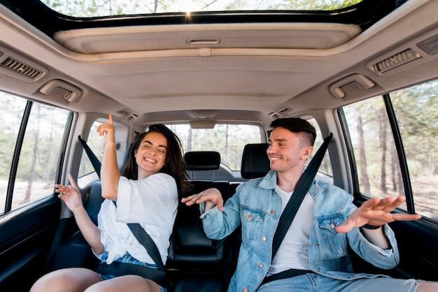 Vista frontal pareja bailando dentro del coche