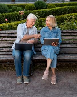 Vista frontal de la pareja en un banco al aire libre con un portátil y una tableta